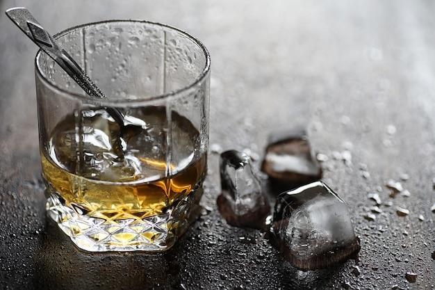 Whisky dans un verre et morceaux de glace sur une table en bois