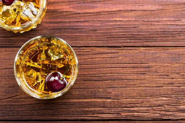 Whisky avec glace et cerise dans deux verres