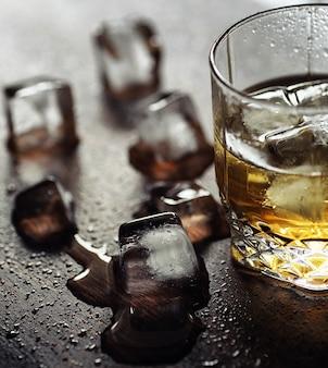 Whisky avec de la glace avec un verre. cubes de glace sur une table en bois et un verre d'alcool fort réfrigéré. table avec whisky américain, bourbon et cartes.