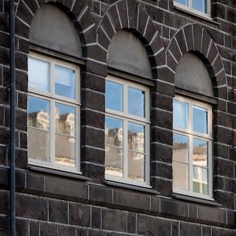 Windows dans un bâtiment en briques reflétant des bâtiments en face