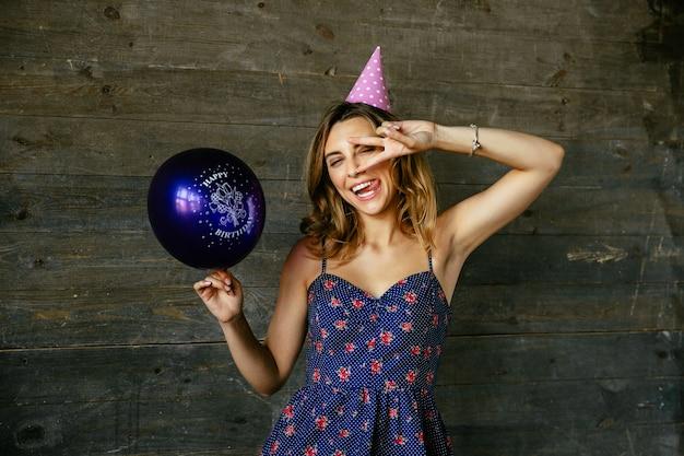 Winking belle anniversaire drôle de célébration, montrant le geste de paix, détient un ballon.