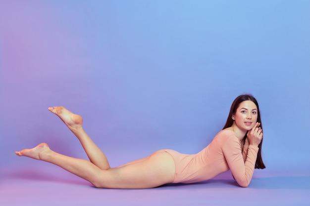 Winsome femelle allongée sur le sol et levant les jambes, portant un body beige, a les cheveux foncés, démontre un corps parfait isolé sur un mur bleu avec une lumière néon rose.