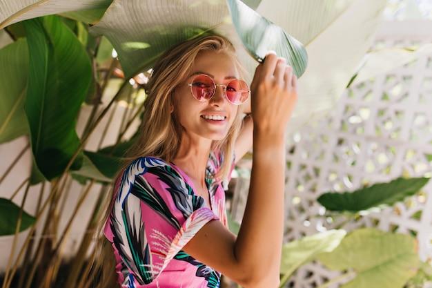 Winsome femme aux cheveux longs dans des lunettes de soleil roses posant à côté des plantes.