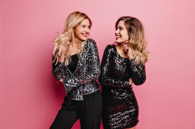 Winsome fille blonde riant avec son meilleur ami. photo intérieure de dames caucasiennes bienheureuses se détendre à la fête.