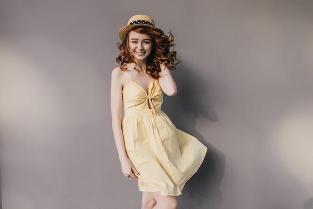 Winsome fille de gingembre au chapeau élégant souriant pendant la séance photo sur le mur gris. photo intérieure d'une femme magnifique mince dans une jolie robe d'été.