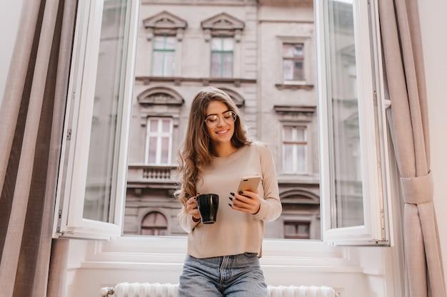 Winsome girl en tenue décontractée, passer du temps à la maison et posant sur fond de ville avec une tasse de thé