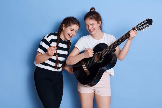 Winsome ladies avec noeud et nattes chantant des chansons et jouant de la guitare