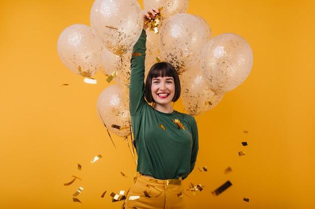 Winsome modèle féminin se détendre à son anniversaire avec un sourire sincère. femme incroyable aux cheveux noirs se détendre après la fête.