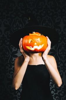 Witch couvrant le visage par la citrouille