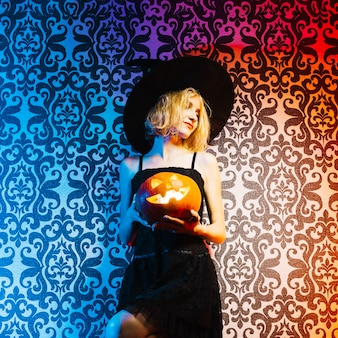 Witch girl holding pumpkin