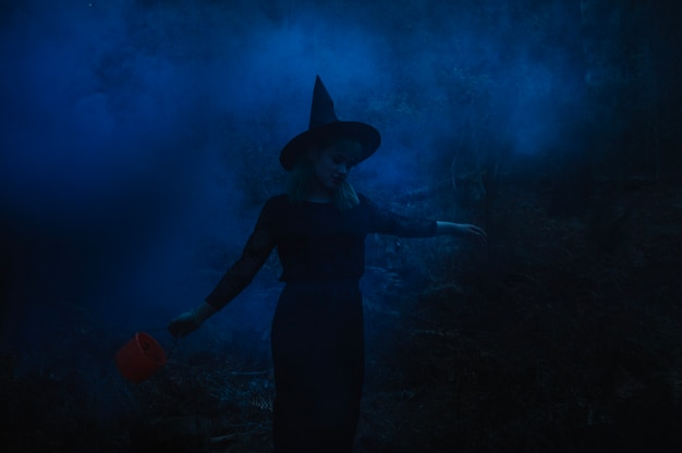 Witch girl with bucket in night forest