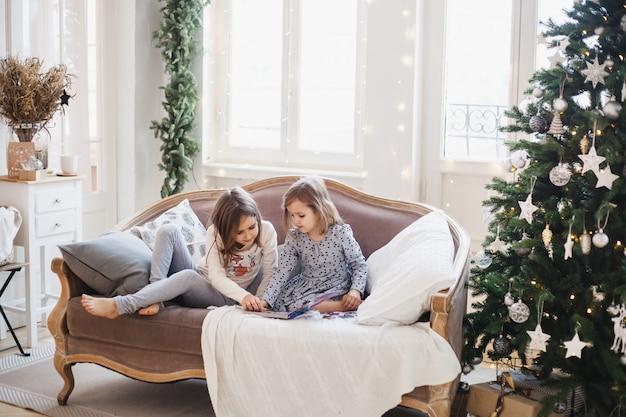 Wo filles assises sur le canapé et feuilletant et lisant un livre, deux soeurs, la chambre est décorée pour noël