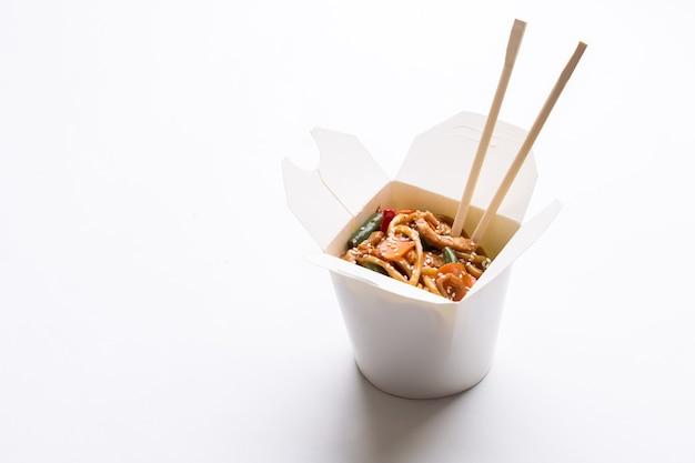 Wok de nouilles dans une boîte en carton sur fond blanc