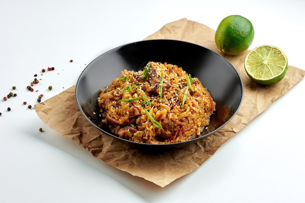 Wok de riz alimentaire de rue asiatique appétissant avec du porc, des piments forts, des légumes, de la coriandre, servi dans une assiette noire sur une assiette blanche