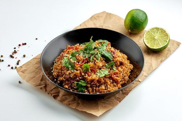 Wok de riz alimentaire de rue asiatique appétissant avec du poulet, des piments forts, des légumes, de la coriandre, servi dans une assiette noire sur une assiette blanche