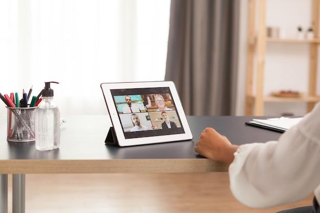 Woma lors d'une vidéoconférence avec des collègues utilisant une tablette tactile.