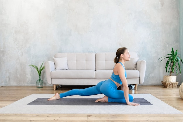 Woman doing matin yoga stretch sur tapis à la maison