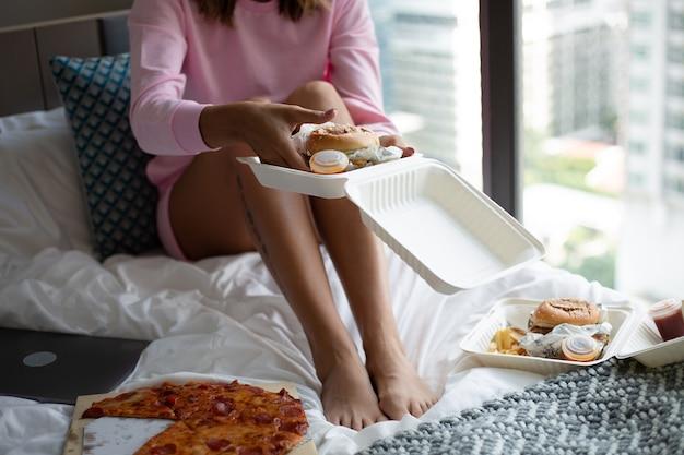 Woman east fast-food à partir de la livraison sur le lit dans la chambre à la maison