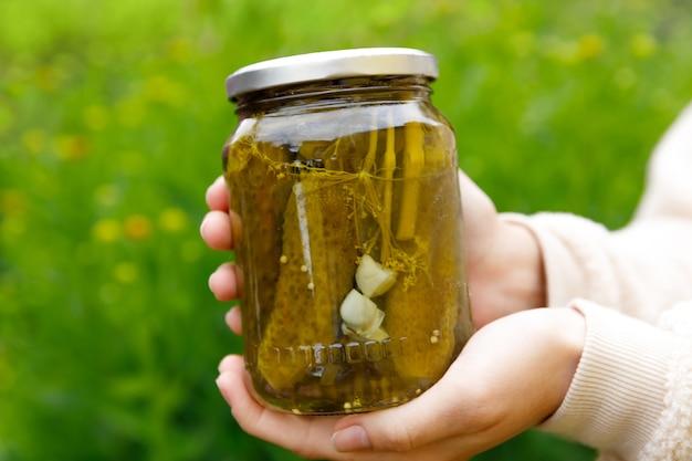 Woman hand holding bocal en verre de concombres marinés préparation domestique marinage et mise en conserve de légumes aliments biologiques d'hiver