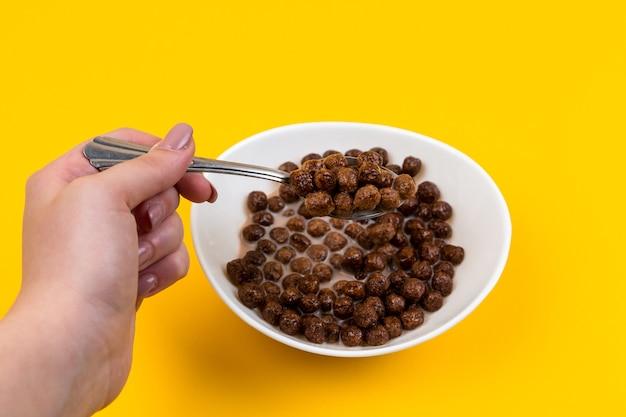 Woman hand holding cuillère au bol blanc avec des boules de céréales de maïs au chocolat et du lait sur jaune