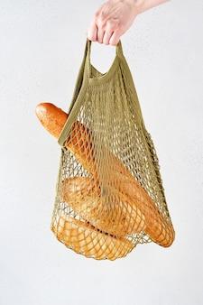 Woman hand holding string shopping ou coton sac en filet réutilisable shopper avec du pain