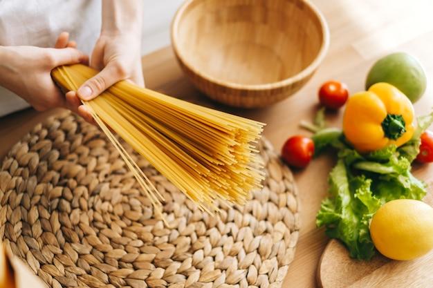Woman hold spaghetti de blé dans les mains