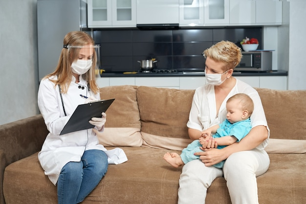 Woman holding baby pendant que le médecin écrit dans le presse-papiers