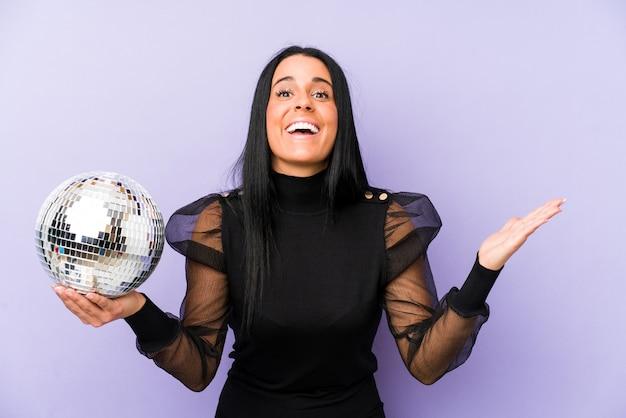 Woman holding a ball party isolé sur mur violet recevant une agréable surprise, excité et levant les mains