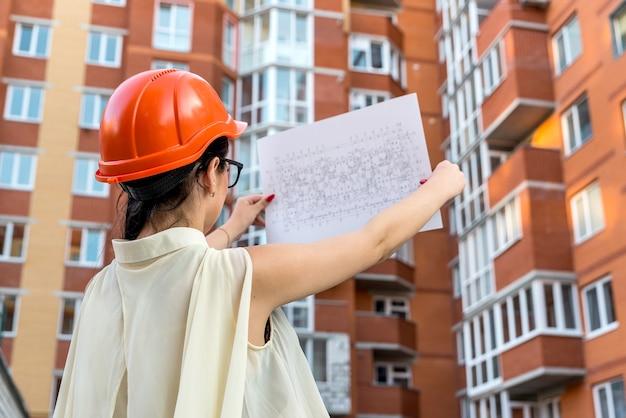 Woman holding blueprint dans les mains et à la recherche dessus