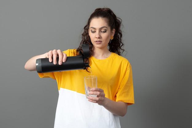 Woman holding eco bouteille d'eau thermo intelligente réutilisable avec rappel de boisson, concept de mode de vie sain