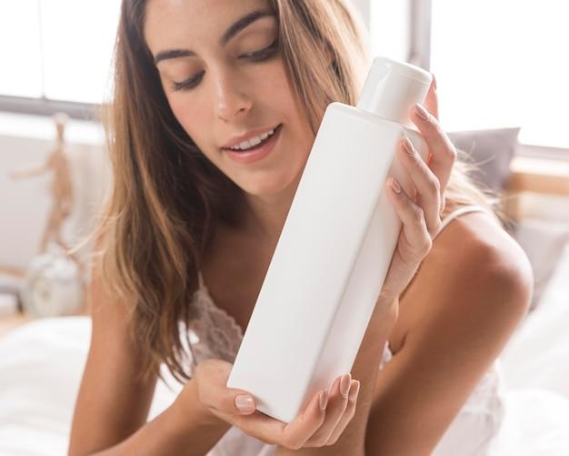 Woman holding lotion pour le corps soins personnels à la maison