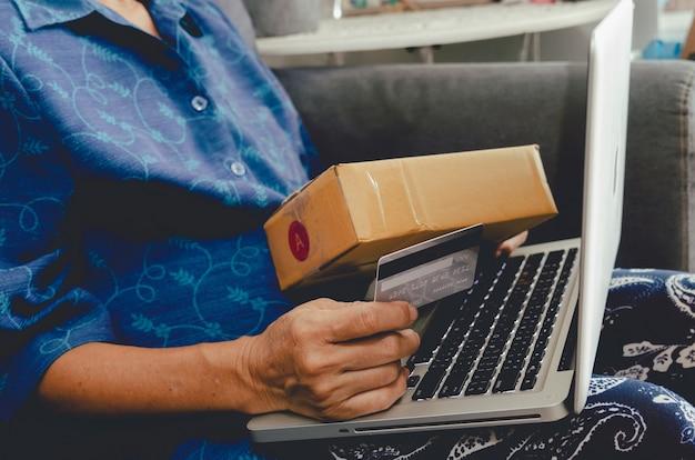 Woman holding post box et carte de crédit achats en ligne e-commerce payant un ordinateur portable à la maison