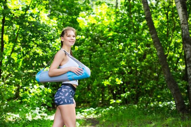 Woman holding roll fitness ou tapis de yoga après avoir travaillé dans le parc
