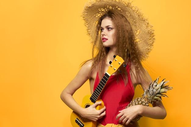 Woman holding ukulele chapeau de paille lifestyle fond jaune exotique