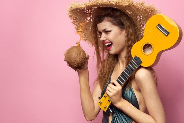 Woman holding ukulele coco cocktail beach hat maillot de bain mode de vie exotique fond rose