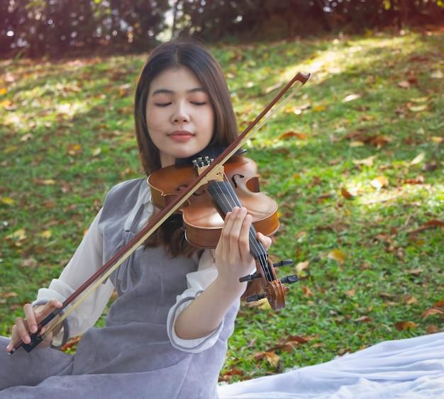 Woman holding violin in hand show comment jouer d'un instrument acoustique