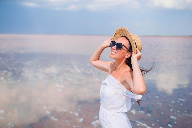 Woman in hat marche sur un lac salé rose sur une journée d'été ensoleillée