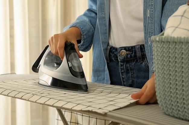 Woman in jeans repassage torchon sur planche à repasser