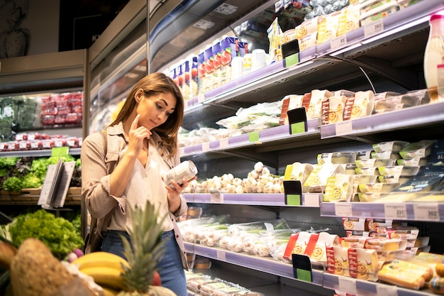 Woman in supermarket lecture des valeurs nutritionnelles d'un produit par l'étagère