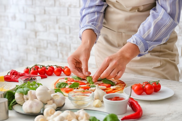 Woman making pizza sur table dans la cuisine