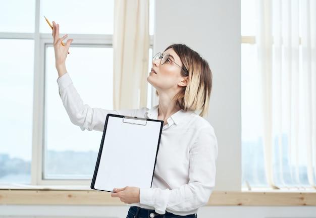 Woman rooming près de la fenêtre montrant un presse-papiers