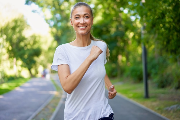Woman running asphalt road summer park active sportive caucasienne femme matin séance d'entraînement concept de mode de vie sain