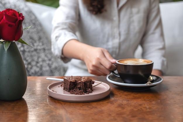 Woman's hand holding et boire du café latte chaud avec un gâteau brownie sur la table