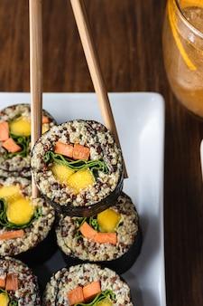 Woman's hand holding sushi roll vegan avec des baguettes en bois