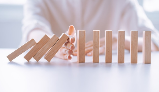 Woman's hand stop effet de crise d'affaires domino en bois, concept de protection contre les risques