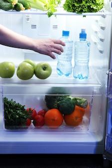 Woman's hand tendre la main pour la nourriture du réfrigérateur, gros plan
