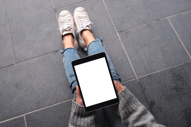Woman's hands holding et à l'aide de tablet pc noir avec écran de bureau blanc vierge