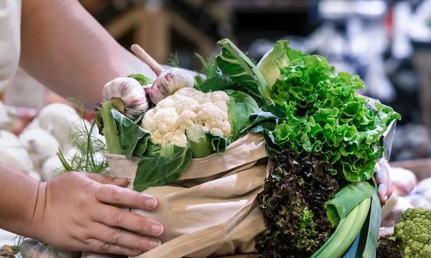 Woman's hands holding brocoli biologique mûr frais, salade de légumes verts et légumes dans un sac en coton au marché fermier du week-end