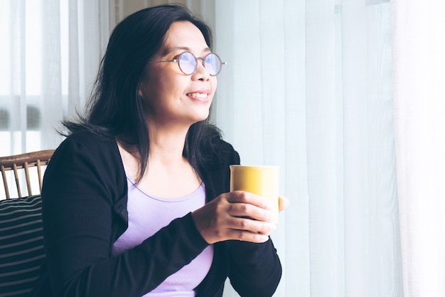 Woman waring glasses holding mug jaune de café assis dans son salon à la maison