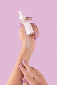 Womans hand holding dropper avec sérum sur fond lavande pastel